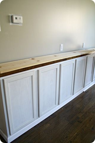 Thrifty Decor Chick started with a long board as the top of  bookcase. The base cab are 12 ft long (four 36 inch cabinets) a 1x12x12 board. To figure out exactly where the supports would go,laid it down on top of the butcher block first: