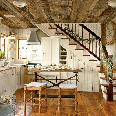 The adorably cozy kitchen, with its simple white cabinetry and walls (and tiny stove and hood!), is home to cookie-making in the winter and lobster boils in the summer. A simple garland studded with local shells adorns with banister, which is fashioned fr