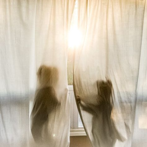 A silhouette of two children playing in curtains. – family life A silhouette of two children playing in curtains.
