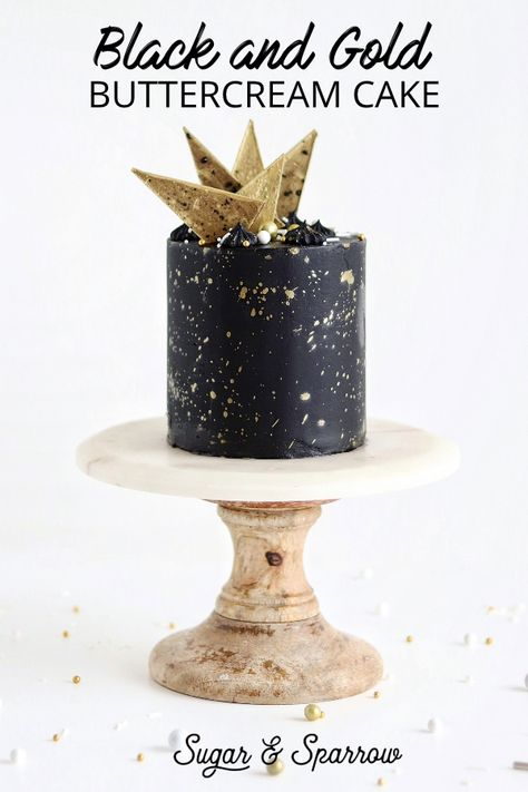 A black buttercream cake with edible gold splatter paint and chocolate geometric shapes (also painted gold!