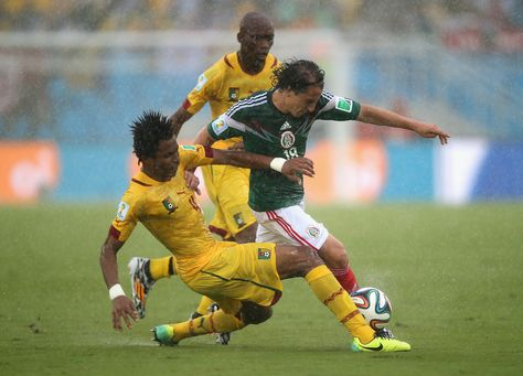 Cedric Djeugoue of Cameroon challenges Andres Guardado of Mexico in the first half during the 2014 FIFA World Cup Brazil Group A match between Mexico and Cameroon at Estadio das Dunas on June 13, 2014 in Natal, Brazil.