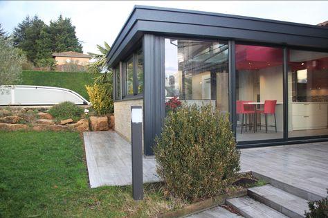 Extension véranda vitrée avec murets en pierre donnant sur terrasse ...