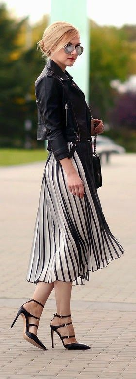 Black and white pleated skirt with leather jacket and black heels.