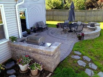 A Beautiful Paver Patio With Stone Seating Walls And A Fire Pit. Behind It  Is A Trex Deck With Trex Handrails, White Vinyl Rails, Black Aluminum Bau2026