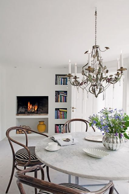 Marble top table, floral chandelier and a fire
