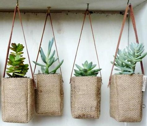 Coffee burlap hanging baskets with leather straps - we love this clever idea for a courtyard garden.