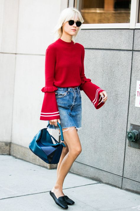 Street style à la Fashion Week pull rouge manches larges mini jupe jeans…