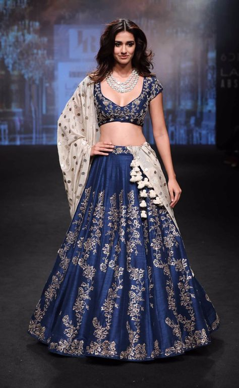 Give yourself an unique look by wearing this exquisite navy blue silk lehenga choli.This spectacular attire is highlighted interestingly heavy embroidery work that gives a divine look to the outfit. Paired with matching blouse and dupatta