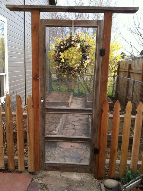 An old repurposed screen door makes a great garden fence idea.