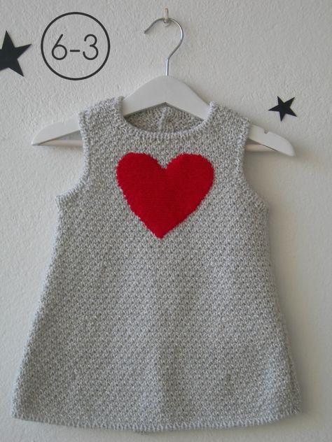 Vestido para bebe hecho a punto fantasía en mezcla de 2 colores con aplicación corazón en punto bobo. Espalda abotonada. Disponible en color camel, gris perla o visón.