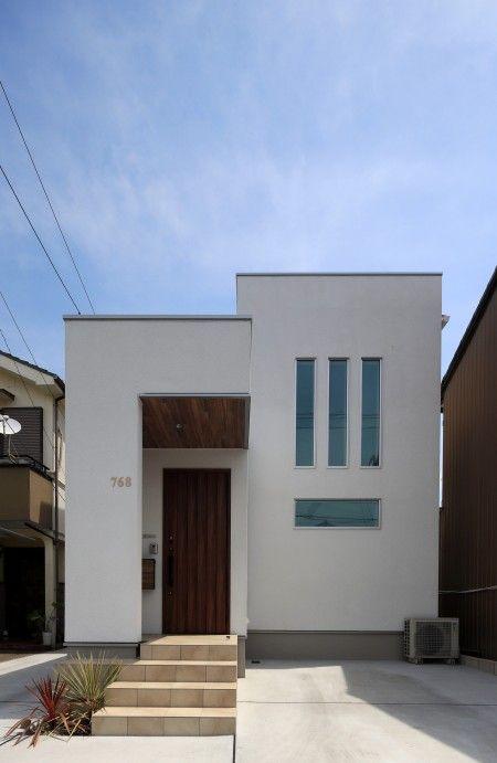白を基調としたシンプルな外観 木目調のドアがアクセント 外観 インテリア 玄関 ドア 玄関ドア スタイリッシュ シンプル ナチュラル シンプルナチュラル シンプルモダン ナチュラルモダン 自然 外構 エクステリア 庭 スタイリッシュモダン 日本住建