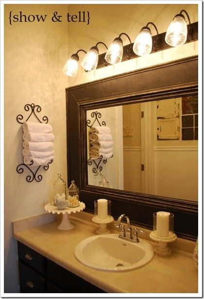 cake plate to store necessities on bathroom counter and candles on each side of sink