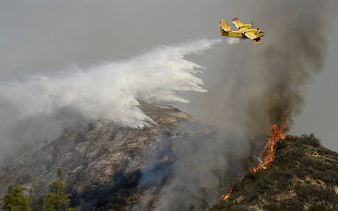 A super scooper air tanker makes waters drops as firefighters battle a fast-moving California wildfire, so-called the Colby Fire, in the hills of Glendora.