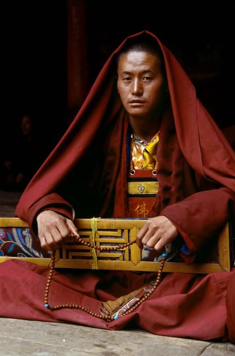Travel Asian people Monk with buddhist text at Gyantse Monastery, Tibet. Photo by Steve McCurry.