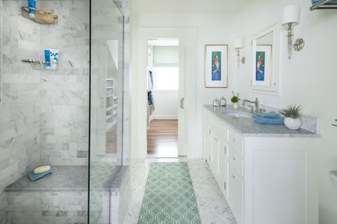 The 6-by-8-foot master bath features a roomy marble-tiled shower with glass walls, and a marble-topped vanity. A pocket door opens to the much-needed walk-in closet. | Photo: Anthony Tieuli