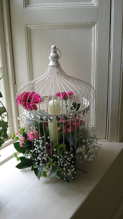 Bird cages enhanced wtih beautiful flowers and candle. perect for the country house hotel or any venue.