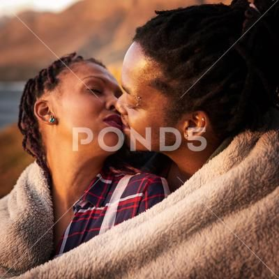 Close up mixed race couple kissing outdoors under a blanket Stock Image #76590986