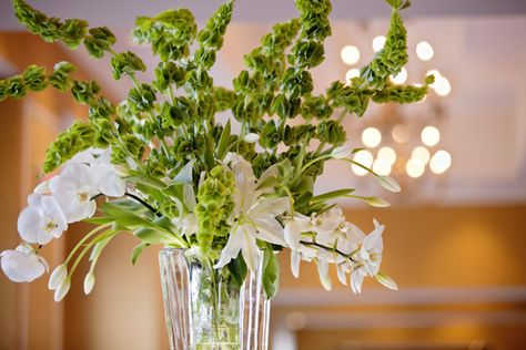 Accent a budget-friendly centerpiece composed of greenery with a few orchid stems