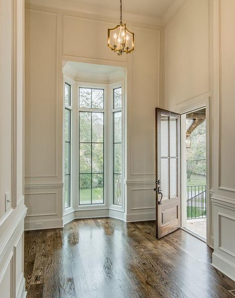 Chic foyer features tall ceiling over full wall wainscoting framing a small bay window illuminating a brass lantern.