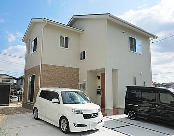 白にレンガ調の外壁で温かみのある外観に 4 5台止められる広々駐車場