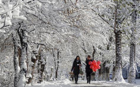 Women walk along a snow-covered road in Almaty, Kazakhstan