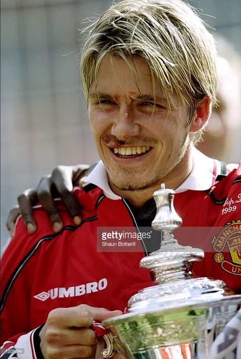 David Beckham of Manchester United celebrates victory with the trophy.