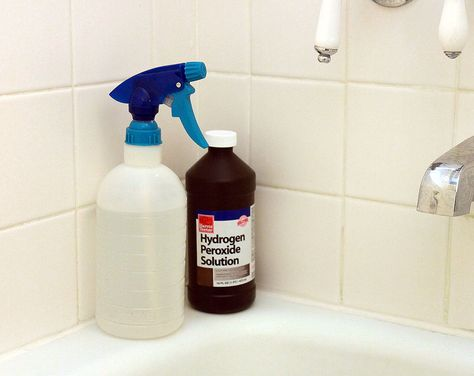 hydrogen peroxide and spray bottle on tub edge