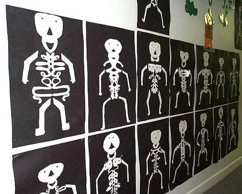 """""""Name Skeletons"""" Look closely:  students folded white paper in half, wrote their names in cursive, and cut out around their names - this formed the body.  They added the head, arms,and legs then mounted their """"name skeletons"""" on black construction paper"""