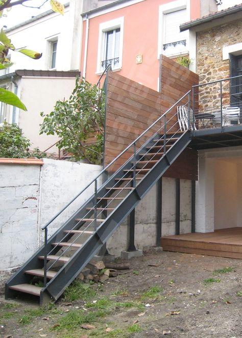 Photo DT108 - ESCA'DROIT®. Escalier droit extérieur design en métal et bois d'accès à une terrasse pour une maison contemporaine. Marches type plateaux bois exotique fixés au limons sur cornière. Limons en extérieur des marches en tôle pliée en 'U'. Rampe contemporaine avec main courante en tube, 3 sous-lisses fines parallèles. Terrasse à l'arrivée de l'escalier composée de longerons UPN recevant des lattes de bois. Pare-vue également réalisé par Escaliers Décors®. - © Photo : Escaliers…