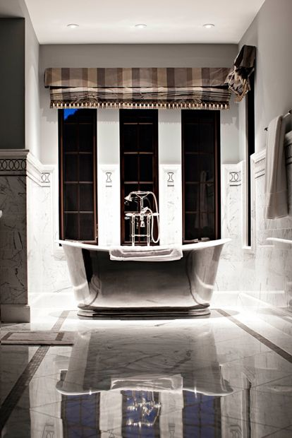 stunningly glamorous bathroom design featuring an incredible waterworks candide oval cast iron bathtub before a wll of windows dressed in