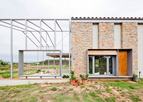 Anna and Eugeni Bach extend gabled stone house with skeletal framework.