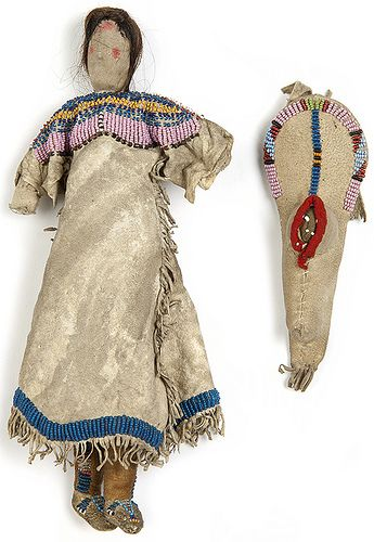 Doll with accompanying cradleboard and infant made by Dakota Indians circa 1880. The adult doll has a sawdust-stuffed cotton body and painted facial features. She wears a fringed buckskin dress with a beaded bodice and hem. Hair is attached to the head; beaded hide moccasins are sewn to the feet. The cradleboard and the infant doll it holds are both trimmed with beadwork and red stroud cloth.
