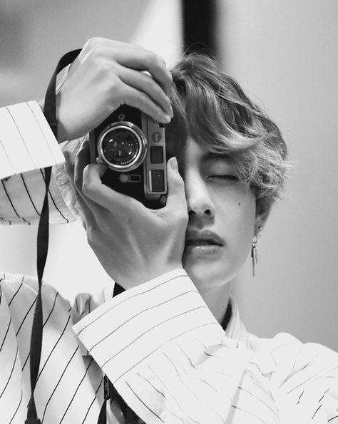 V (BTS) tạo dáng bên máy ảnh của anh ấy.
