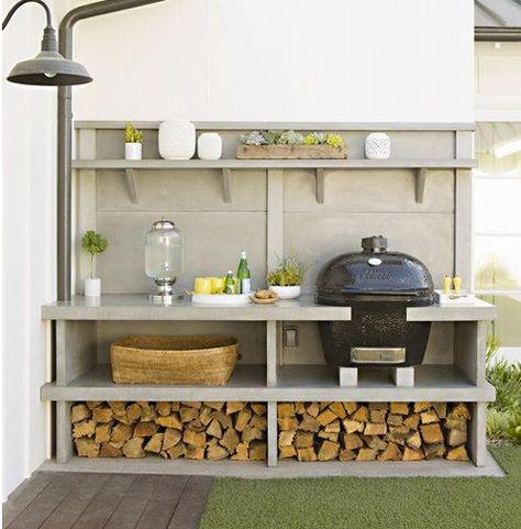 Dans la cuisine d'été le barbecue est intégré dans une plaque de béton préfabriqué
