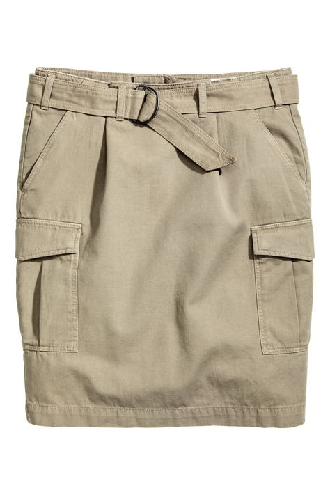 Skirt in sturdy cotton twill with a detachable belt with a metal buckle, concealed zip at the back, side pockets and patch pockets with a flap and concealed