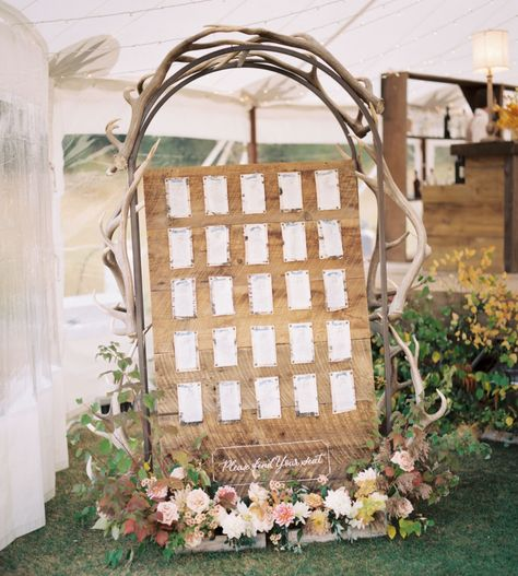 At this Montana ranch wedding reception, the seating chart was framed by elk antlers, with each table assignment pinned to a plywood board. We love the added large pink, white, and yellow flowers at the base. Click through for more rustic wedding ideas! #rusticwedding #ranchwedding #seatingchart #weddingreception #weddingreceptionideas
