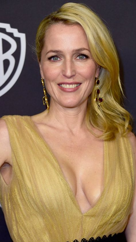 Gillian Anderson glamorous red carpet smile in a golden gown with a deep low plunging neck, star of The X-Files, Hannibal, and American Gods, a modern classic beauty.