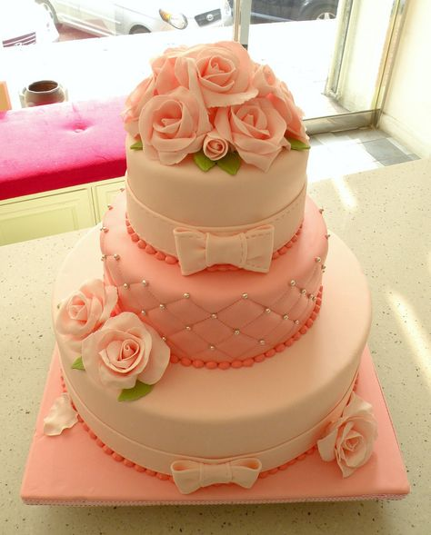 An abundance of large roses on this cake, with a quilted tier and tiers with bows.