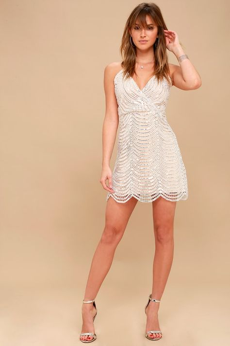 Lulus Exclusive! The Lulus Lele White and Silver Sequin Mini Dress is all about besties and bubbly! Shiny silver sequins and white embroidery create an eye-catching design over a nude knit lining, as it shapes a plunging surplice bodice. Fitted waist and flirty sheath skirt with a scalloped hem. Adjustable spaghetti straps and exposed silver back zipper/clasp. Fit: This garment fits true to size. Length: Above mid-thigh. Size small measures 29.5 from adjustable straps to hem. Bust: Great for an