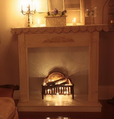 faux fireplace - salvaged mantle, old cast iron fireplace grate, twigs and birch logs with christmas lights tucked all around