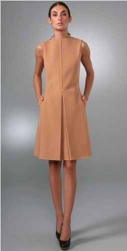 This wide-neck, sleeveless wool dress features inverted pleats at the skirt and seam details at the front and sides. On-seam hip pockets and…