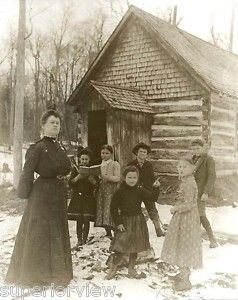 This photo shows teacher with her students, in front of a rustic, one room schoolhouse in the U.P. of Michigan.