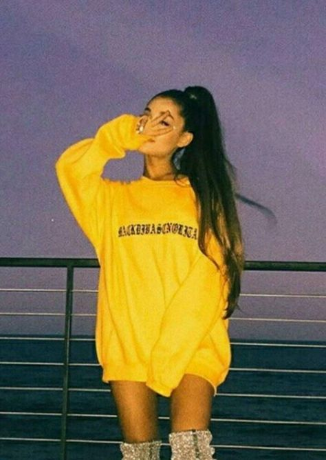 Ariana Grande gave the peace hand sign to the lens while she's wearing a yellow oversized printed sweater.