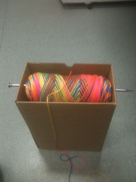 Ingenious way to hold your yarn while knitting or crocheting: box, one large knitting needle, and yarn.