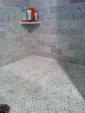 carrera marble subway tiles on walls. floor in carerra marble in chevron or herringbone pattern.