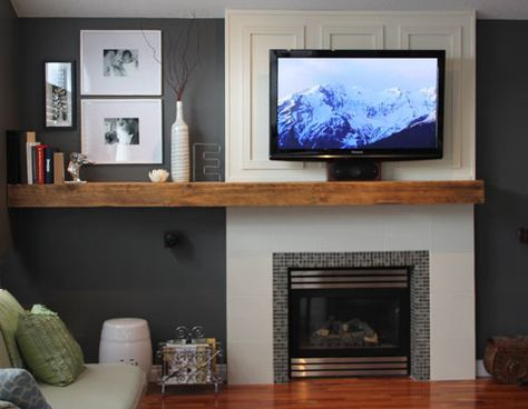 Off-center chunky mantel, tile below and drywall bump-out above to make a continuous column (and recess the TV mount). They wired the TV through the wall into the next room to hide the components.