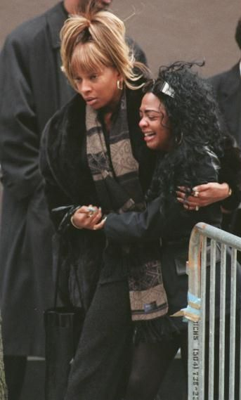 Lil' Kim being comforted by Mary J. Blige after Biggie's funeral in Lil Kim being comforted by Mary J Blige after Biggies funeral in 1997