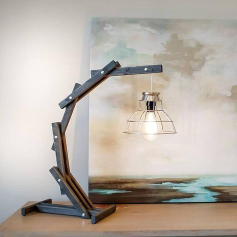 This industrial gray wood arc table lamp beautifully illuminates your desk or favorite reading spot with a soft, glowing light. This rustic wood desk lamp is hand crafted with stained wood and silver hardware. Pair with our Rustic Arc Floor Lamp:
