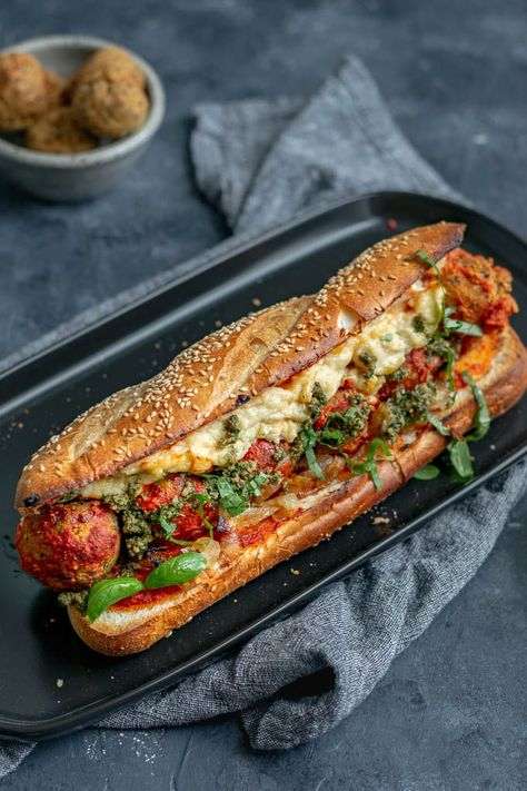 These mouth watering baked meatball subs are completely vegan! Stuffed with easy chickpea meatballs, marinara, pesto, and homemade vegan mozzarella.