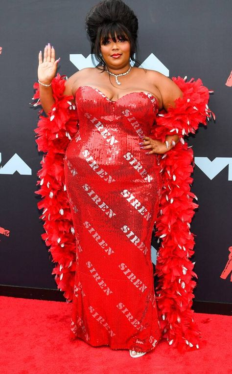 Lizzo from Best Dressed Celebrities at the 2019 MTV VMAs Red hot, hot, hot! Lizzo stuns at the star-studded ceremony with this flashy and flamboyant gown by Moschino. And like the words emblazoned on her dress, she is a